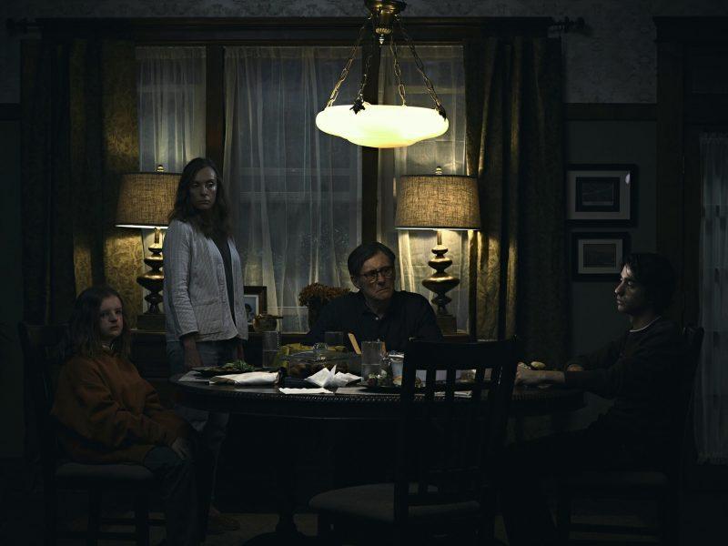 Familie Graham sitzt am Tisch, sehr dunkel, düstere Atmosphäre. Szenenbild aus Hereditary, einem der besten A24-Filme.