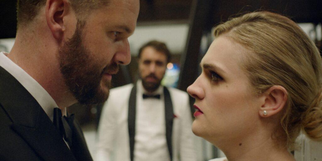 Auf der Hochzeit in The Climb blicken Kyle und Marissa einander tief in die Augen. Hintergründig steht Mike zwischen ihnen.