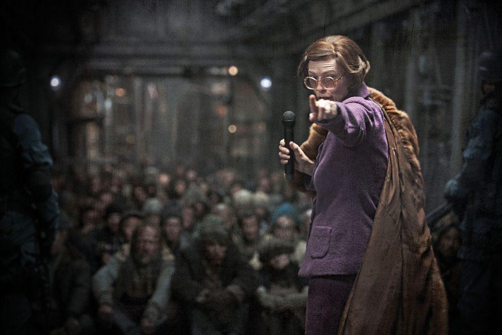 Tilda Swinton als Teil der Elite und Befehlshaberin steht vor der Unterschicht mit einem Mikrofon