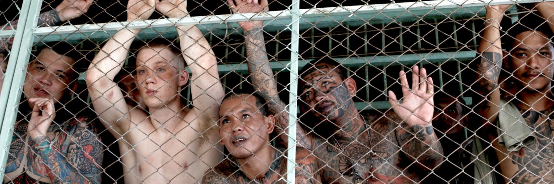 Billy steht mit einigen Insassen hinter einem Gitter, er sieht verzweifelt aus, die anderen lachen