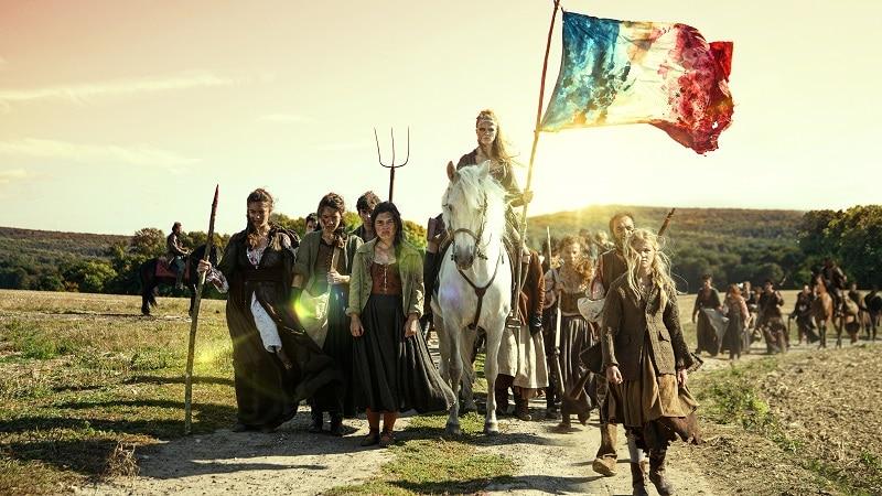 Angeführt von einer Frau auf weißem Pferd, die die französische Flagge hochhält, ziehen die bewaffneten Bürger und Bauern über den Feldweg, um für ihre Freiheit zu kämpfen in La Révolution - Neu auf Netflix im Oktober 2020