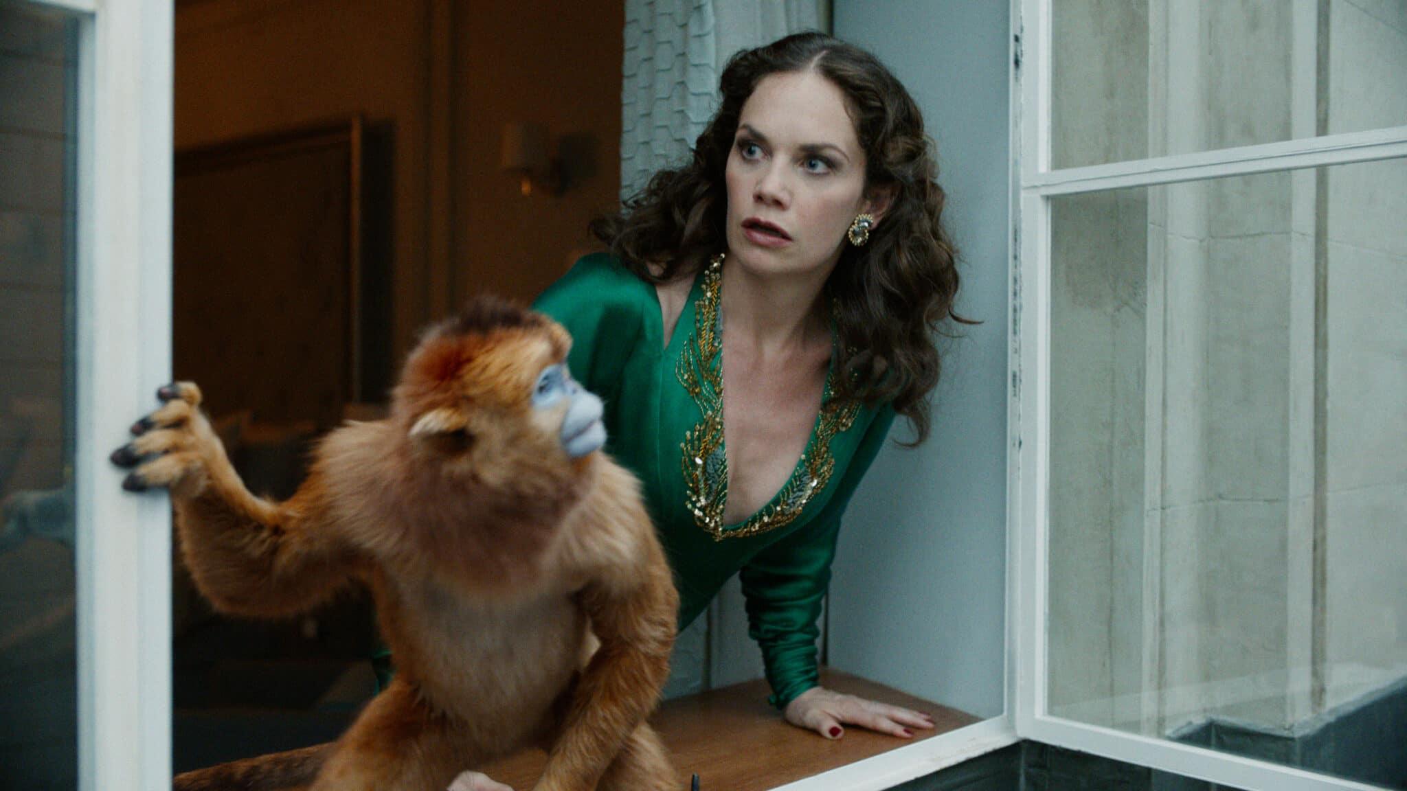 Ms. Coulter (Ruth Wilson) blickt erschrocken aus dem Fenster. Sie trägt ein grünes Kleid und vor ihr auf dem Sims sitzt ein Affe.