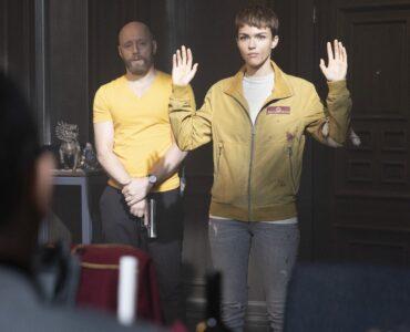 Ruby Rose streckt ihre Hände hoch, hinter ihr ein bewaffneter Gangster, der sie ruhig betrachtet, während ihnen Jean Reno gegenübersitzt - Neu auf Sky im Juli 2021