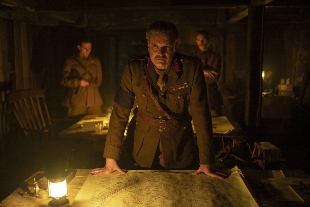 Gernal Erinmore (Colin Firth) betraut die Soldaten Blake und Schofield in einem Bunker mit ihrem gefährlichen Auftrag. Vor ihm liegt eine Landkarte und der Raum wird nur durch das schwache Licht einiger Laternen beleuchtet in 1917.