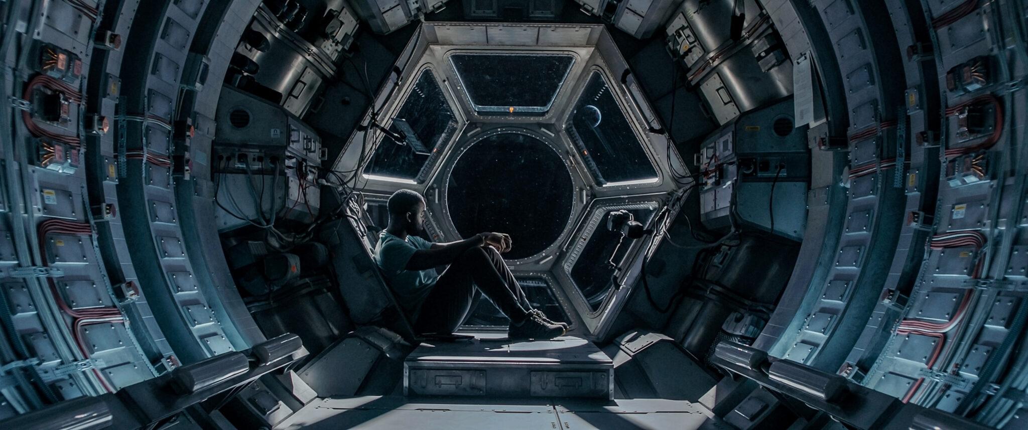 Michael (Shamier Anderson) sitzt im Raumschiff vor einem sechseckigen Fenster und blickt in die Weiten des Alls. Der Raum ist rund und voll mit technischen Geräten.