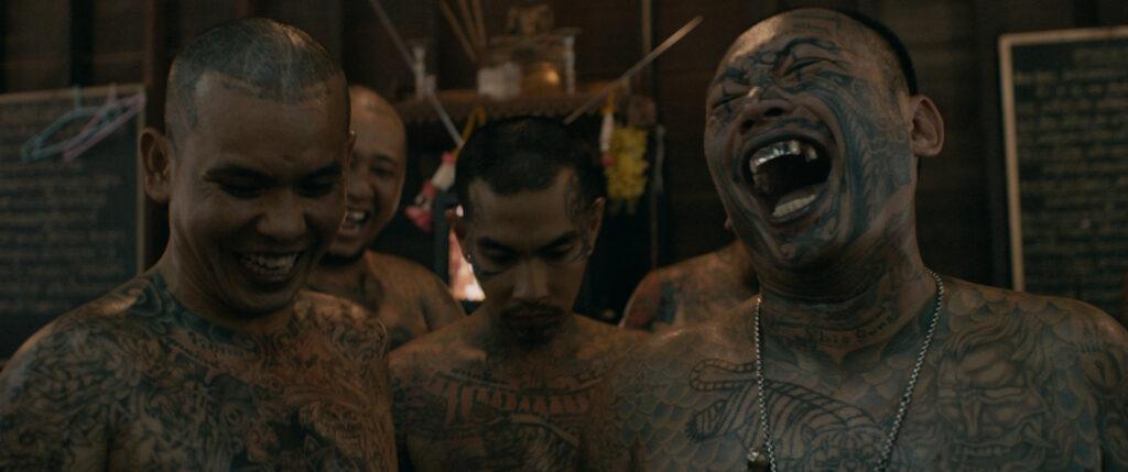 Drei Insassen stehen in einem Halbkreis zur Kamera, sie alle lachen und sehen nach unten
