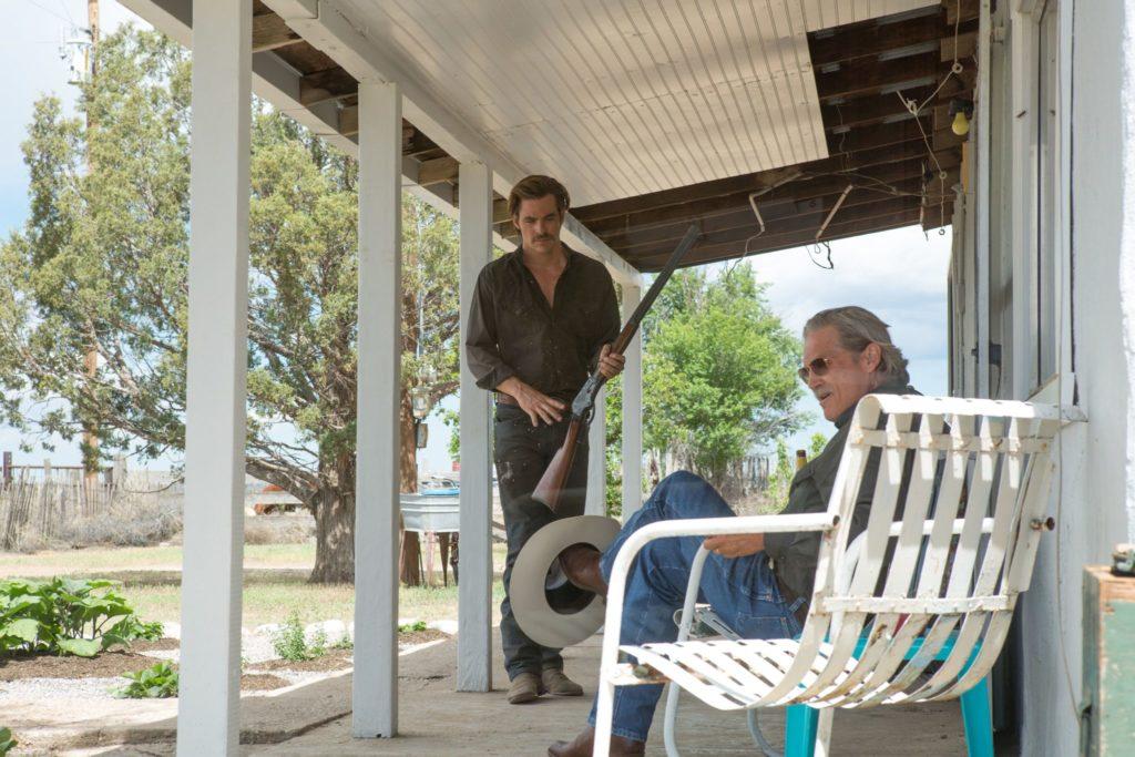 Sherrif Marcus sitzt auf der Veranda, Toby steht ihm mit einem Gewehr in der Hand gegenüber in Hell or High Water
