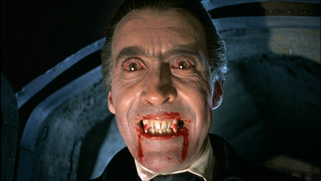 Christopher Lee hat als Blutsauger Graf Dracula die Augen weit aufgerissen, während Blut aus den Lefzen des gräulichen Gesichts fließt - Hammer Horrorfilme