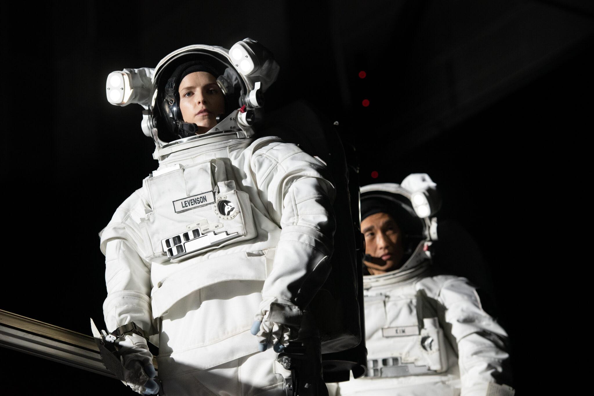 Anna Kendrick und Daniel Dae Kim in ihren weißen Astronautenanzügen hintereinander vor dem schwarzen Hintergrund des Weltalls.