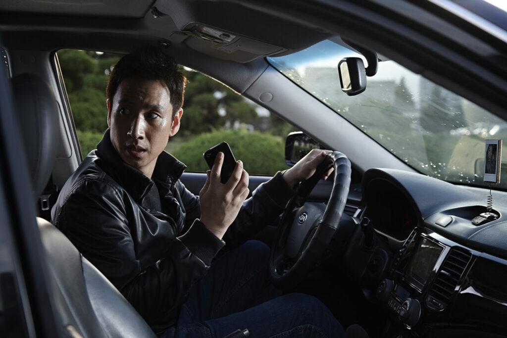 Der Protagonist sitzt in seinem Auto mit einem Handy in der rechten Hand. Besorgt blickt er über seine rechte Schulter nach hinten.