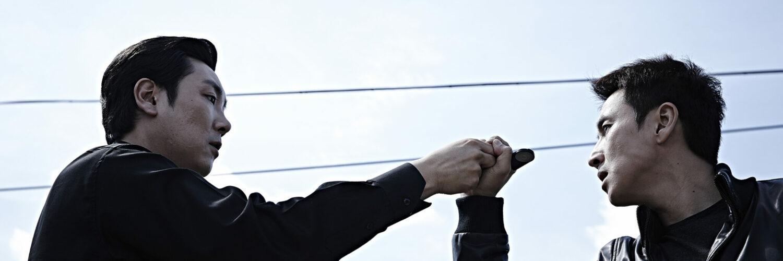 Der Gegenspieler auf der rechten Bildseite hält der Hauptfigur nicht näher definierbares, schwarzes Objekt vor sein Gesicht. Mit der rechten Hand unterstützt der Protagonist die Haltrichtung des Kontrahenten. Die Figuren sind seitlich in einer Nahaufnahme in der unteren Hälfte des Bildes angeordnet. Im Hintergrund ist ein leicht wolkiger Himmel erkennbar und die Kabel eines Strommastes durchlaufen das Bild.