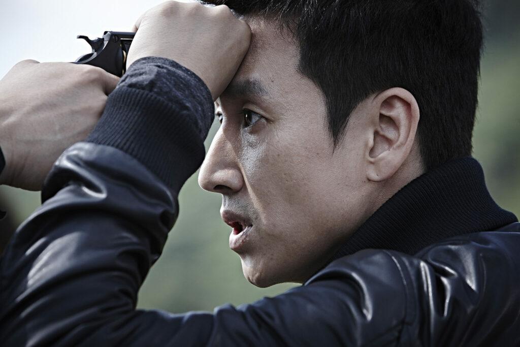In einer Nahaufnahme unterstützt der Protagonist in Profilansicht die Laufrichtung der Waffe seines Kontrahenten an die eigene Stirn. Sein Gesicht nimmt die rechte Bildhälfte ein.