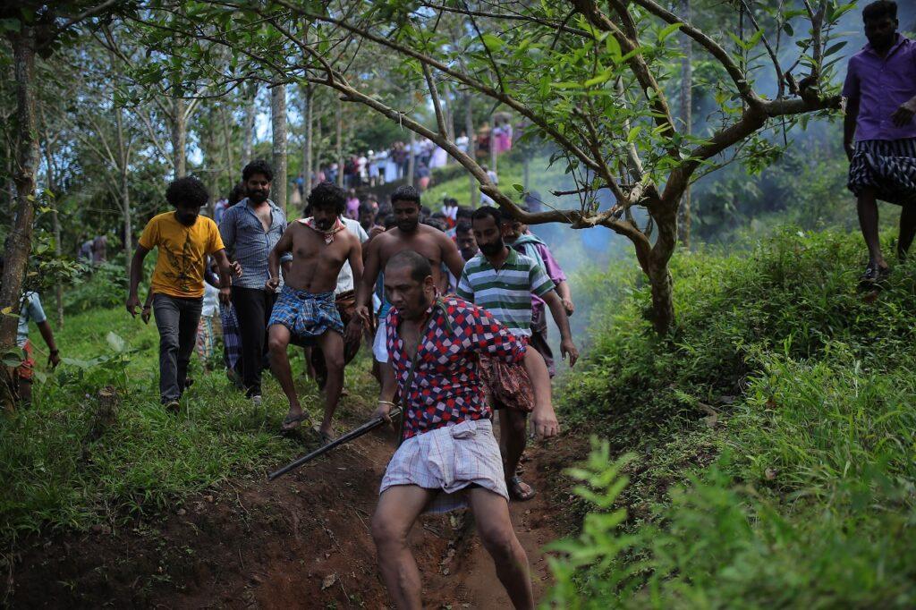 Viele Männer folgen den Jäger Kuttachan durch den Wald - Zorn der Bestien - Jallikattu