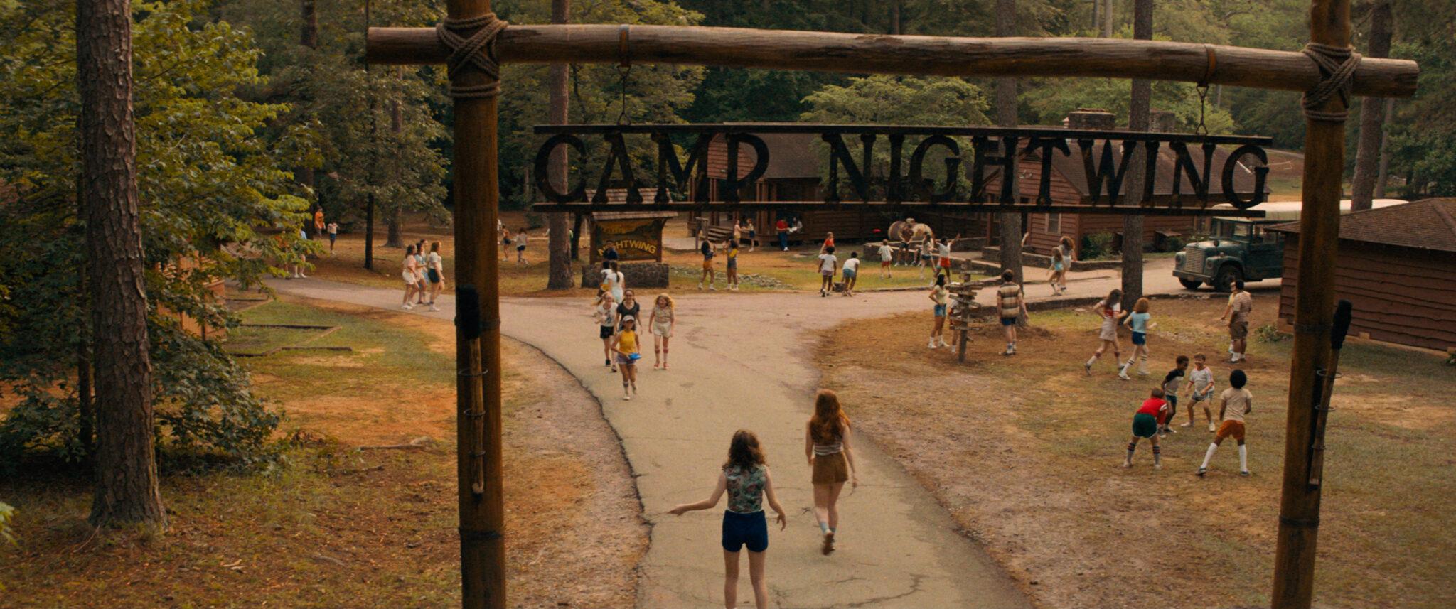 """Man sieht eine Zufahrtsstraße in einem Waldstück zwischen Blockhütten aus Holz. Zahlreiche Kinder spielen auf den anliegenden Wiesen oder laufen auf dem Weg. Im Vordergrund sieht man das Schild mit dem Namen des Camps """"Camp Nightwing"""""""