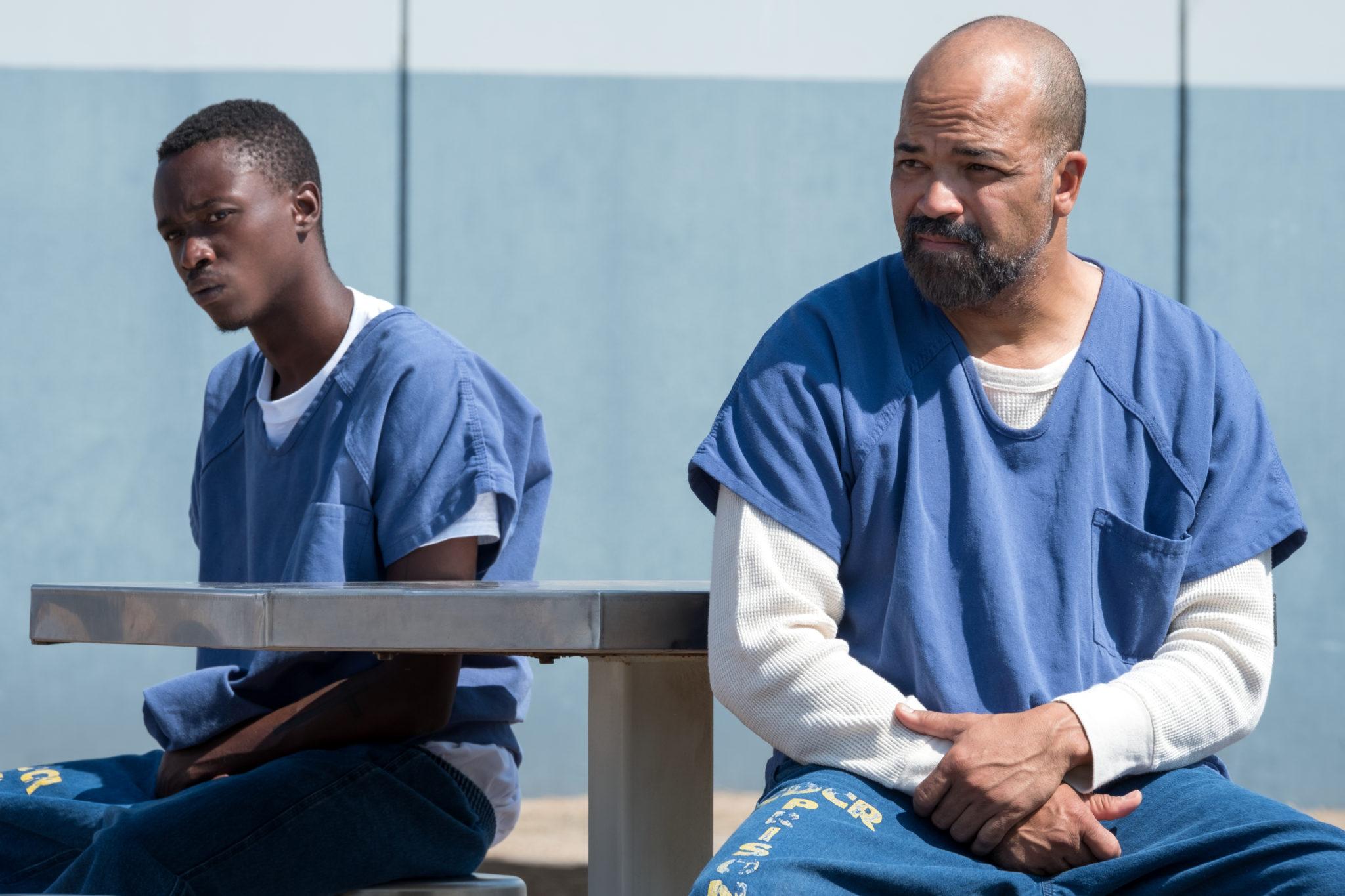 Vater und Sohn sitzen zusammen im Außenbereich des Gefängnisses in All Day and a Night. Sie tragen die typische blaue Klamotte von Insassen und gucken, von der Sonne geblendet, nach links aus dem Bildbereich.