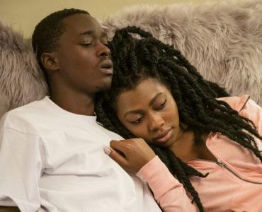 Jakhor und Shantaye liegen zusammen auf einer flauschigen Couch in All Day and a Night. Shantaye kuschelt sich dabei an Jakhors Schulter, der bedrückt aussieht.
