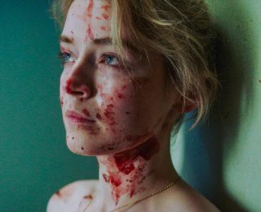 Sarah lehnt an einer Wand. Sie ist blutverschmiert und scheint über etwas nachzudenken.