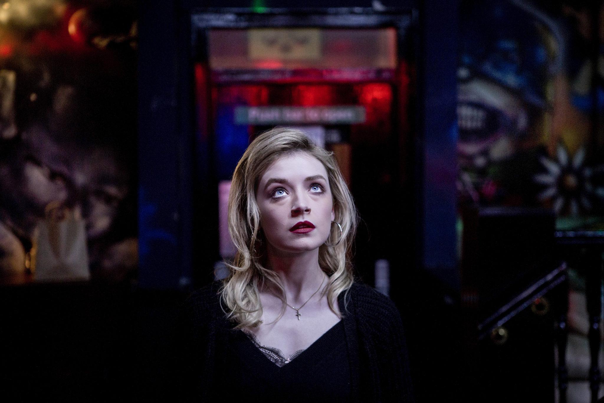 Sarah steht aufgebrezelt vor einem unscharfen Hintergrund, der einen Nachtclub suggeriert. Die einzige Lichtquelle ist auf sie gerichtet.
