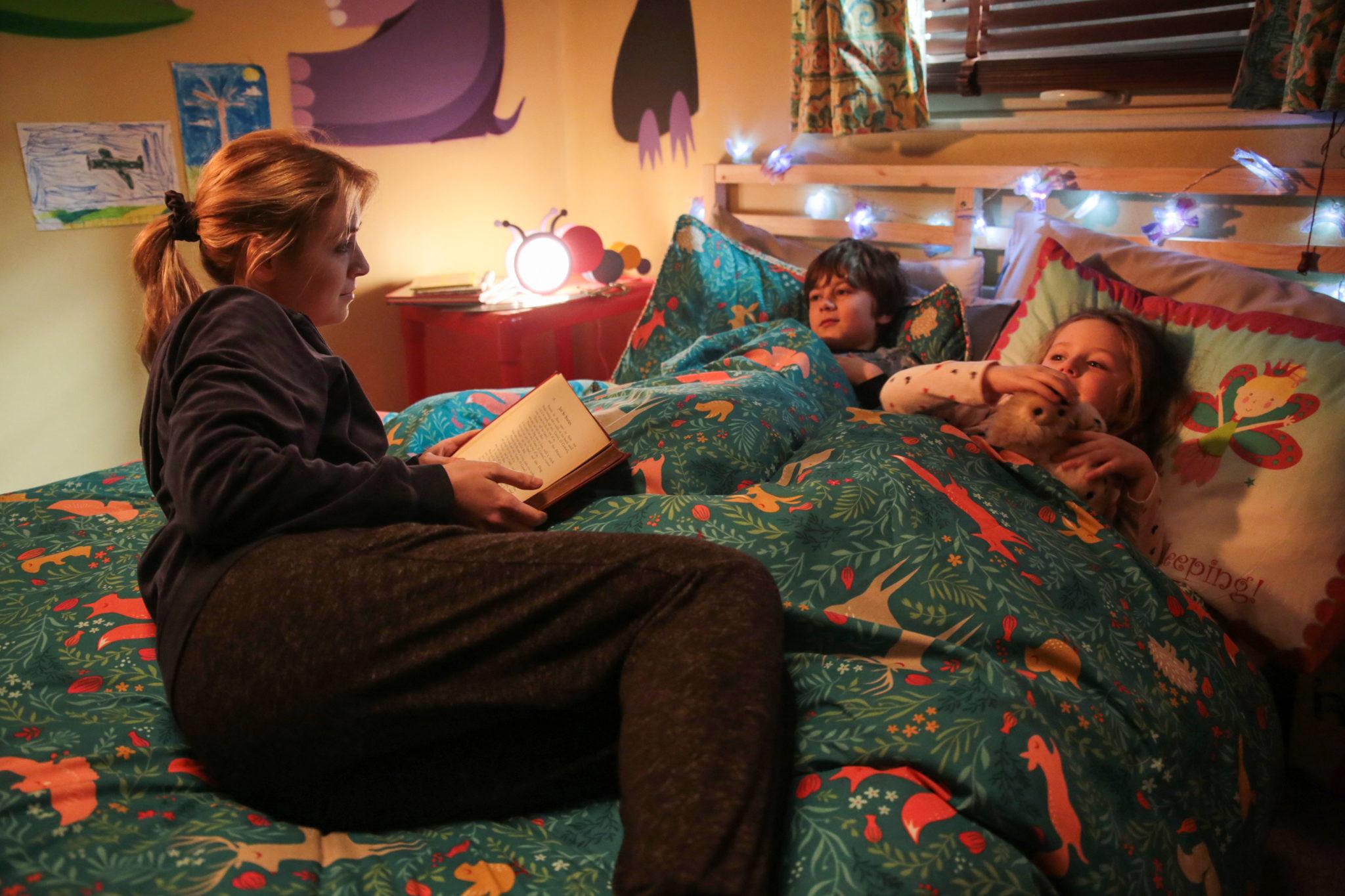 Im Kinderzimmer liest Sarah ihren kleinen Kindern etwas vor. Die beiden liegen zugedeckt im Bett. Eine Lichterkette schmückt das Zimmer.