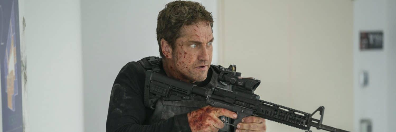 Mike Banning (Gerard Butler) hält blutverschmiert eine automatische Waffe im Anschlag und blickt entschlossen Richtung seinem Ziel.