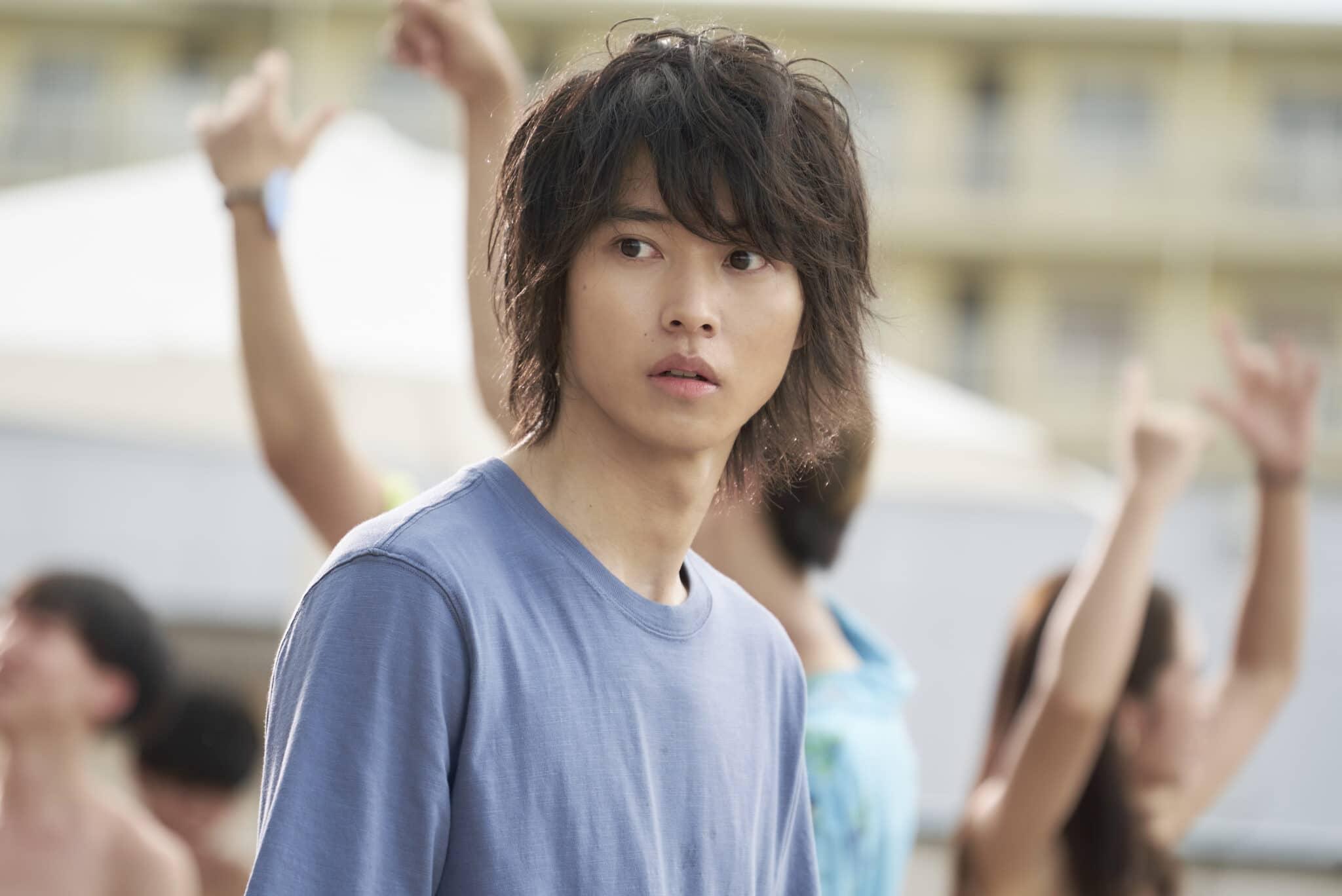 Arisu (Kento Yamazaki) schaut erstaunt. Im Hintergrund sieht man feiernde Menschen.
