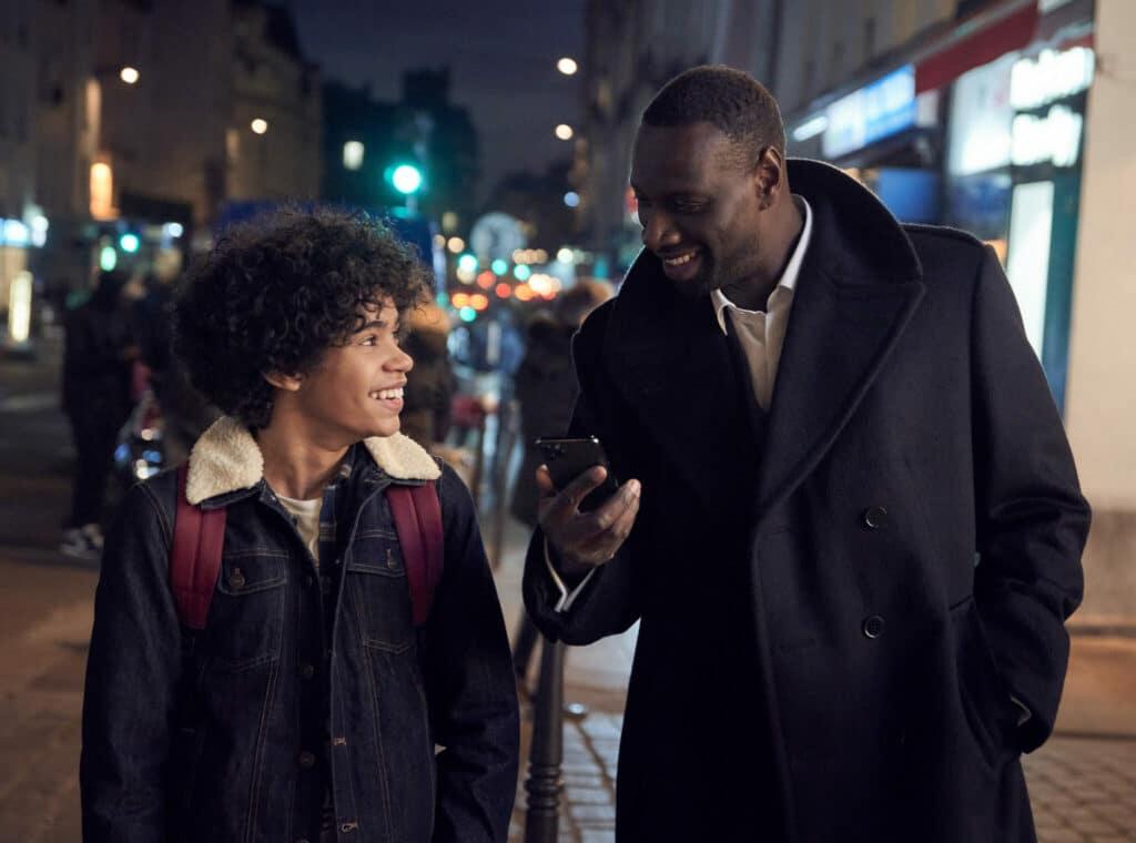 Assane Diop steht rechts neben seinem Sohn Raoul und zeigt ihm etwas auf seinem Handy in Lupin.