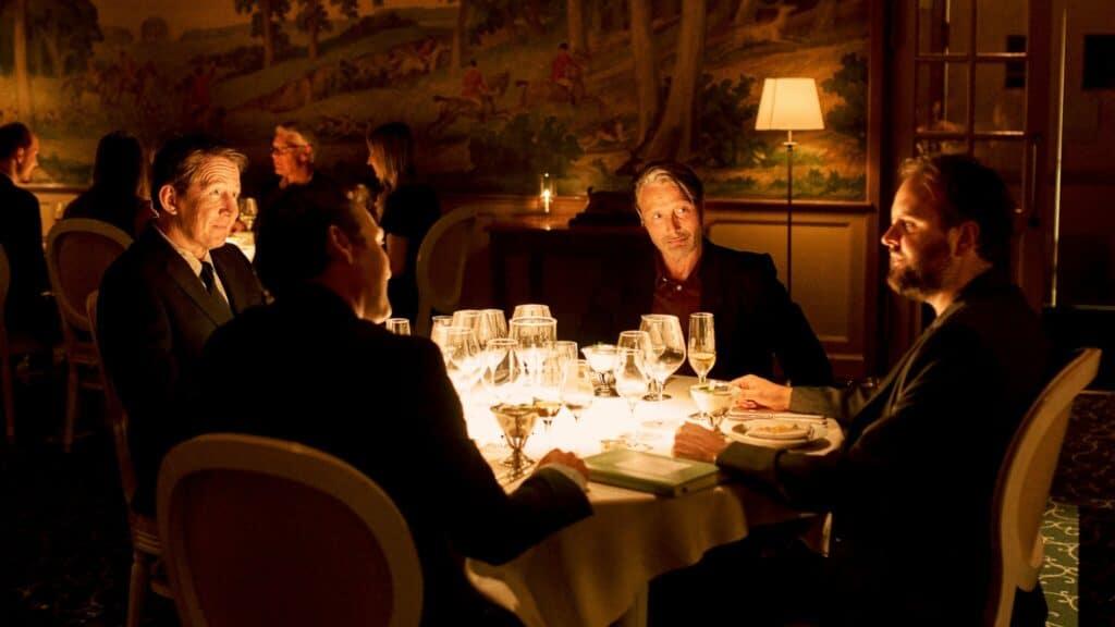 Martin, Tommy, Peter und Nikolaj sitzen gemeinsam an einem Tisch im Restaurant und unterhalten sich, während Sekt und Bier auf dem Tisch steht. Another Round ist der Abschlussfilm des Film Fstival Cologne 2020