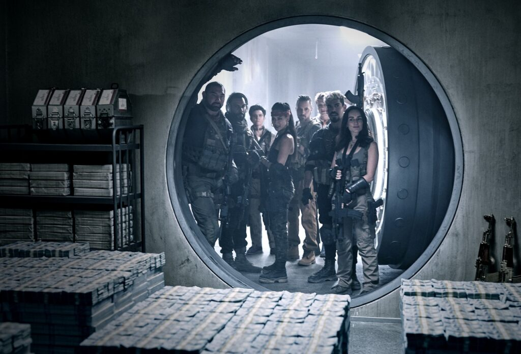 Dave Bautista lehnt im Eingang des riesigen Safes, seine Mannschaft blickt zufrieden auf die Paletten voller Dollar-Noten im Innern - Neu auf Netflix im Mai 2021