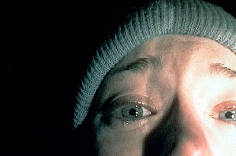 Das mit einer Taschenlampe beleuchtete, entsetzte Gesicht einer jungen Frau in The Blair Witch Project - Neu bei Prime im Oktober 2020