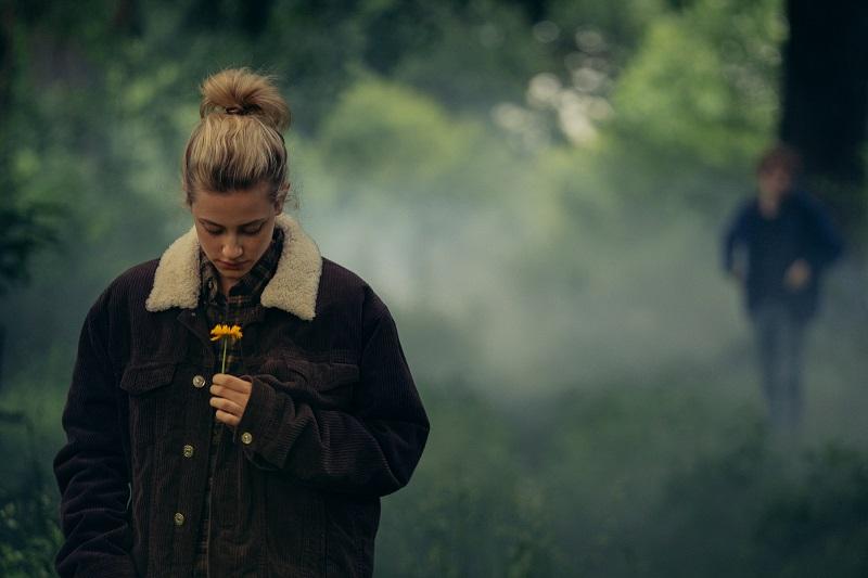 Eine junge Frau steht im Vordergrund, riecht an einer Blume; hinter ihr sieht man eine Gestalt im trüben Nebel - Neu auf Prime im August 2020