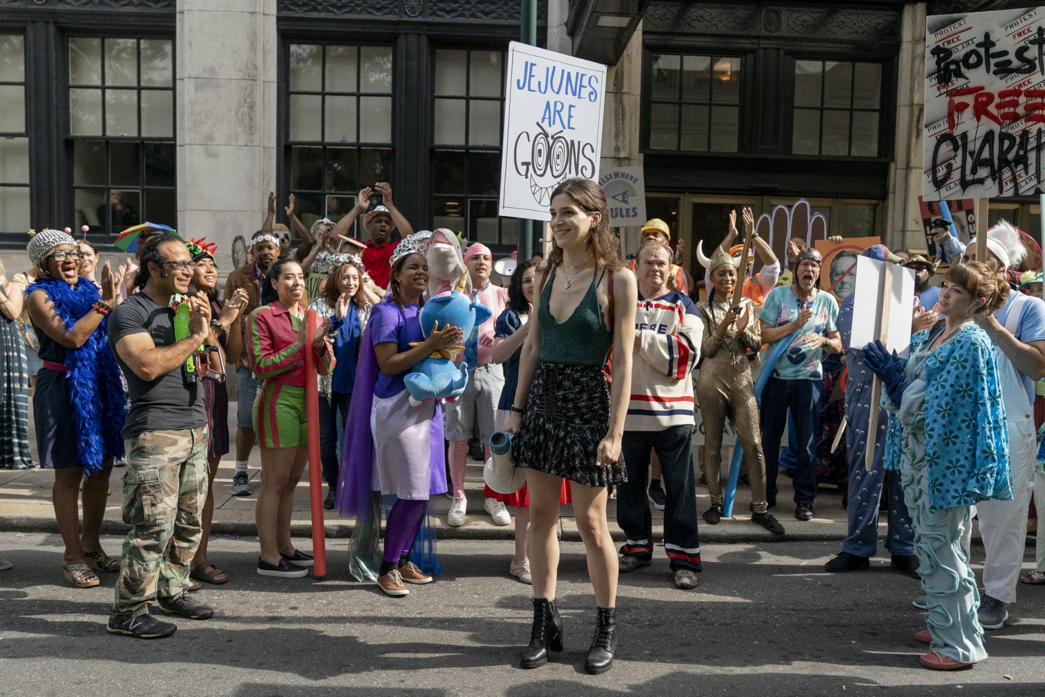 Simone steht glücklich im Mittelpunkt einer bunt gemischten Gruppe applaudierender Demonstranten in Dispatches from Elsewhere