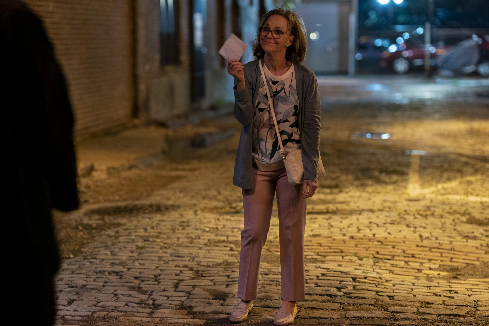 Janice steht in einer nächtlichen Seitenstraße auf Kopfsteinpflaster, sie lächelt zufrieden und hält einen Briefumschlag in der Hand in Dispatches from Elsewhere