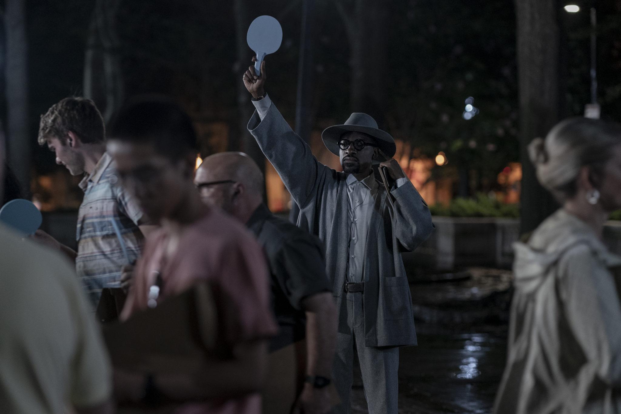 Der in einem pfahlen blauen Anzug gekleidete Afro-Amerikaner Fredwynn steht nachts in einer Menschentraube und versucht mittles eines erhobenen Schildchens auf sich aufmerksam zu machen