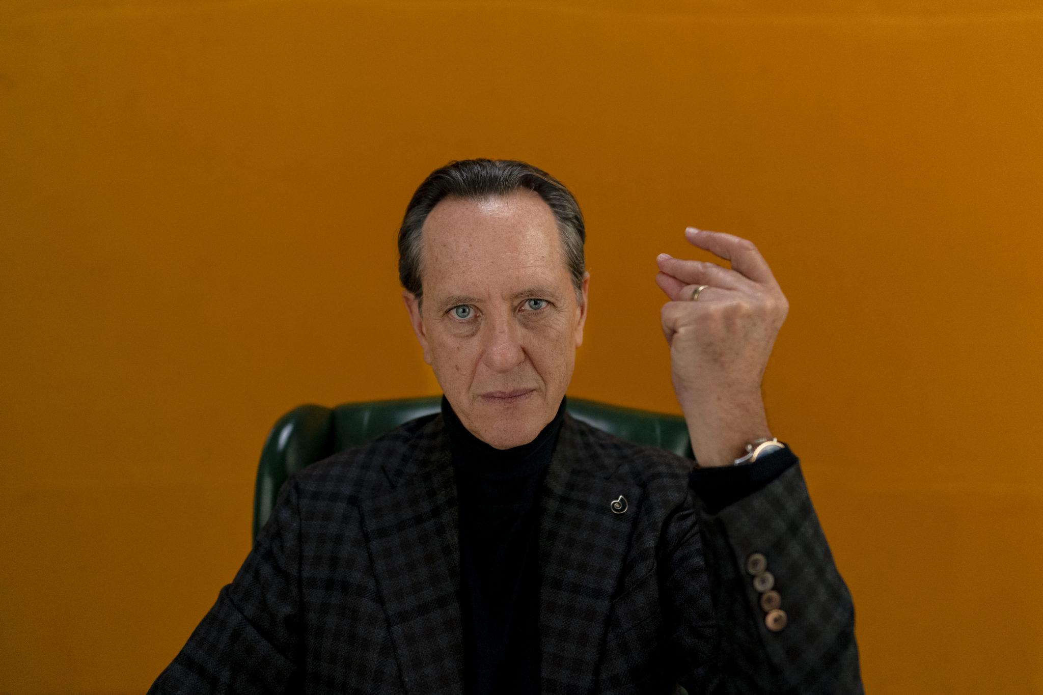 Erzähler Octavio sitzt in einem Sessel vor einer orangen Wand und schnippt mit dem Finger der erhobenen linken Hand in Dispatches from Elsewhere
