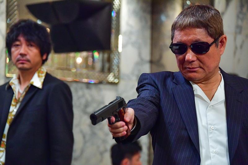 Yakuza Otomo trägt Anzug und Sonnenbrille und richtet seine Waffe auf jemanden - Neu bei Prime im August 2020