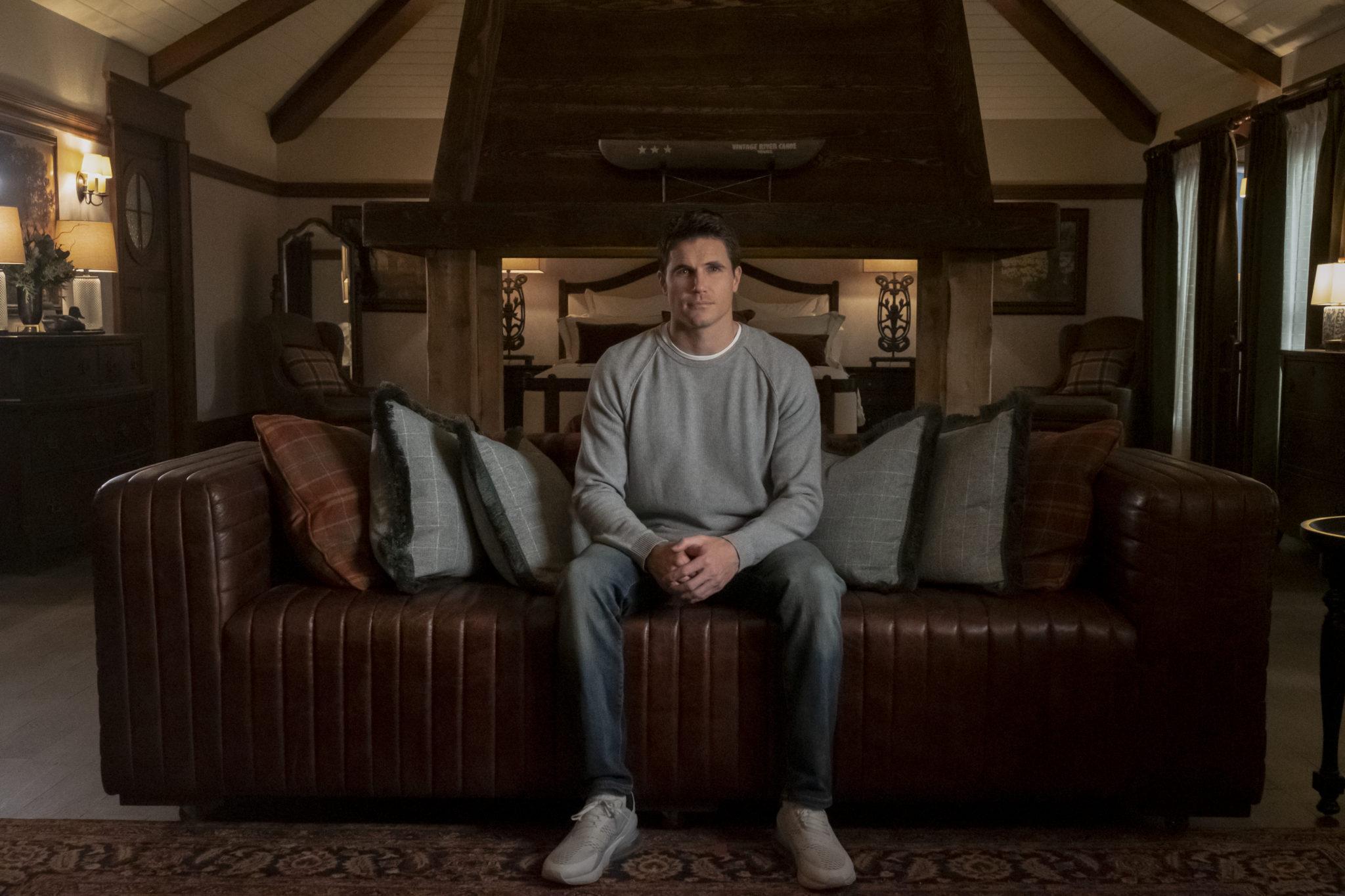 Nathan sitzt nachdenklich auf seiner Couch in seinem schönen, neuen Heim im Lake View Resort in Upload