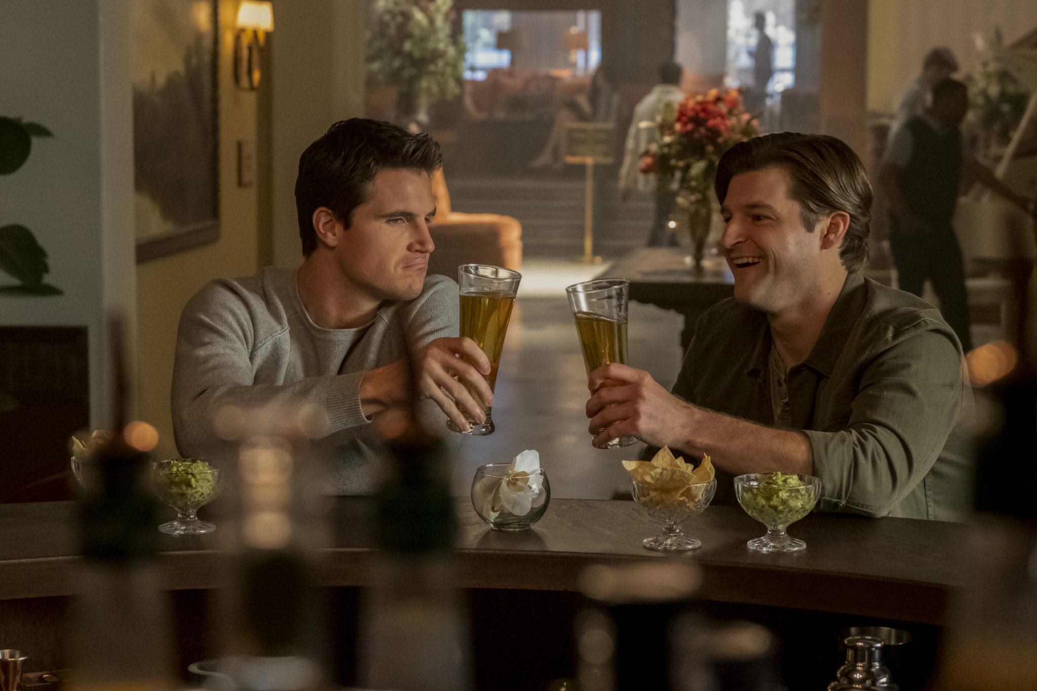 Nathan und Luke stoßen an der Bar mit einem Glas Bier an in Upload