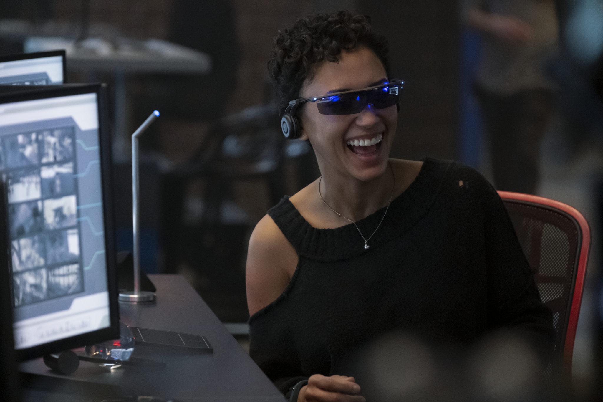 Nora hat eine VR-Brille auf und lacht, hat gerade sichtlich Spaß bei der Arbeit