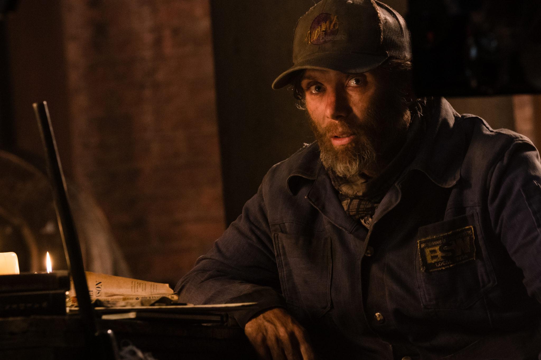 Cillian Murphy in A Quiet Place 2 als Emmett. Er trägt Basecap und Vollbart und sitzt an einem spärlich beleuchteten Tisch.