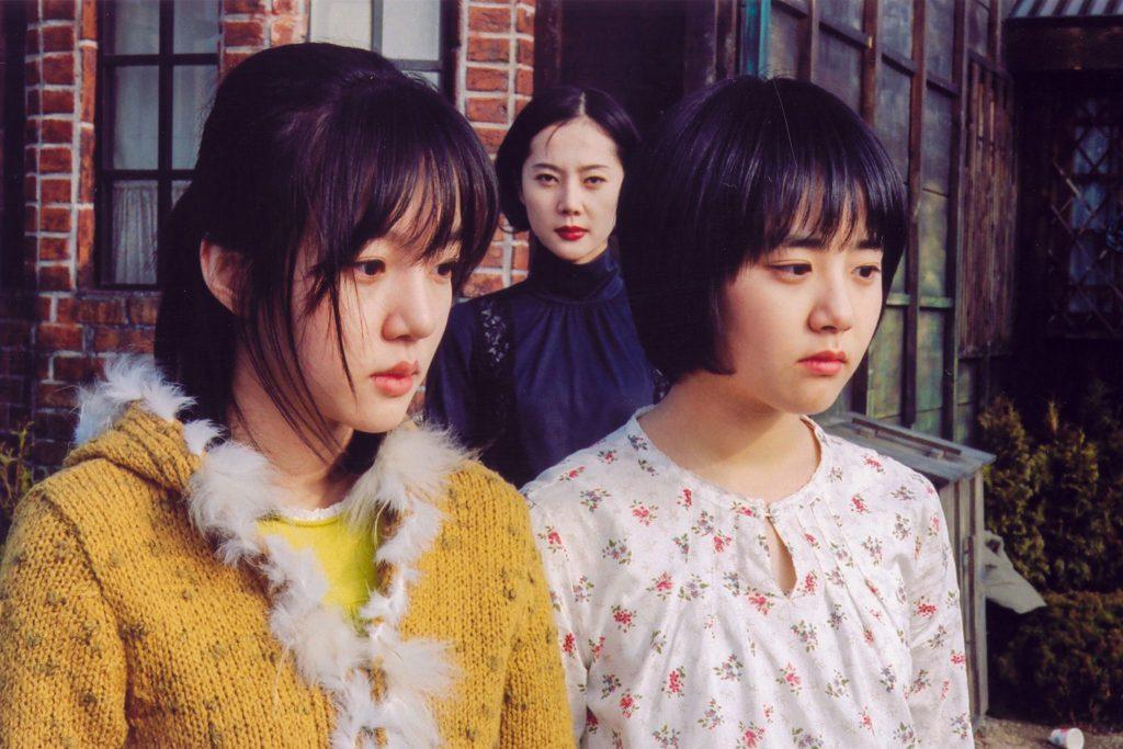 Die beiden Schwestern schauen traurig und im Hintergrund schaut die Stiefmutter genau in die Kamera - A Tale of Two Sisters