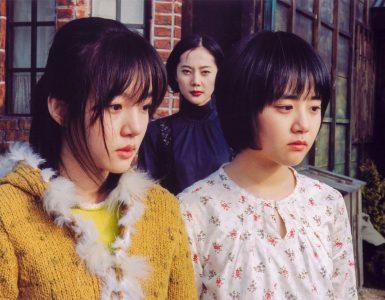 Die beiden Schwestern schauen traurig und im Hintergrund schaut die Stiefmutter genau in die Kamera