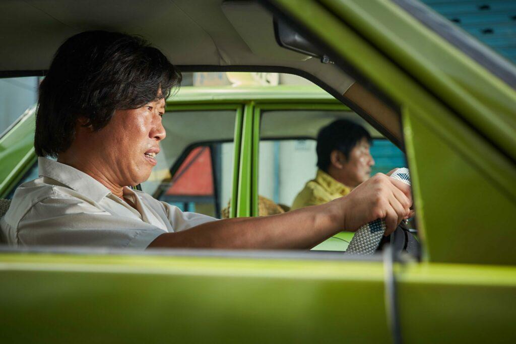 Ein Kollege Kim Man-seop sitzt auf der linken Seite des Bildes vor dem Lenkrad seines Taxis. Ab seinem Seitenfenster ist der Protagonist ebenso in seinem Fahrzeug zu sehen.