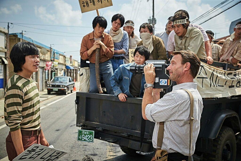 Vor dem Hintergrund eines Transportwagens mit Protestanten hält Hinzpeter seine Kamera auf einen Protestierenden, der sich auf der linken Seite des Bildes befindet.