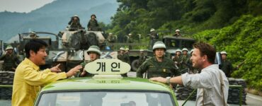 Der Taxifahrer steht auf der linken Seite seinem Fahrgast Jürgen Hinzpeter gegenüber. Zwischen ihnen steht das grüne Taxi und im Bildhintergrund das Militär.
