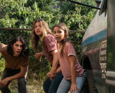 Noah, Jill und Matilda verschanzen sich hinter einem Lieferwagen.
