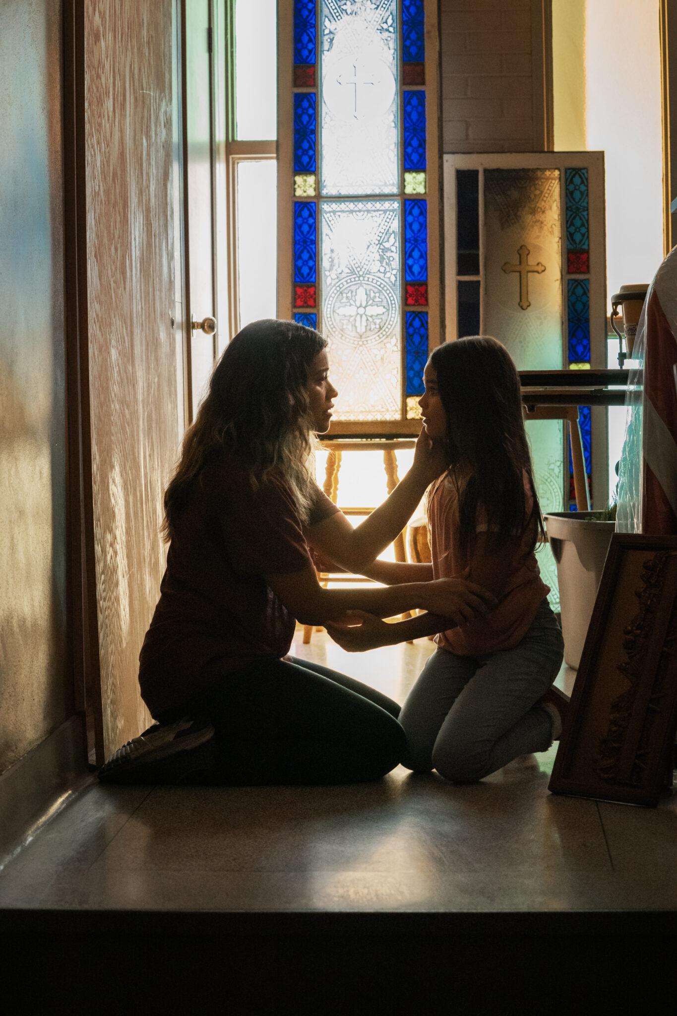 Jill und Matilda knien in einem Kirchenraum vor einem bunten Fenster. Die Mutter hält die Tochter an den Armen und scheint ihr etwas ernstes mitzuteilen.