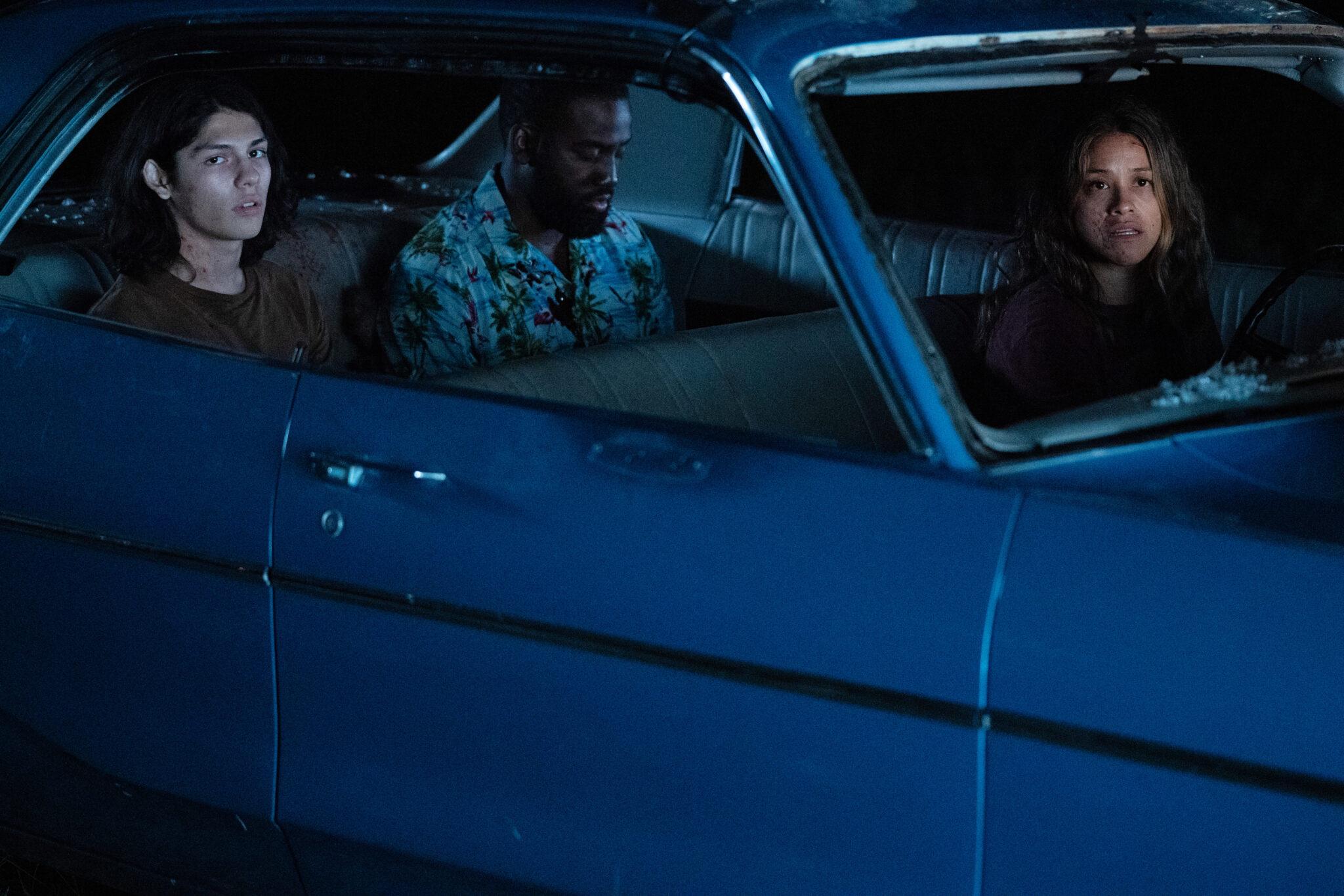 In einem blauen Wagen sitzen Noah, Dodge und Jill (von links nach rechts). Es ist nachts und alle tragen den Schrecken im Gesicht.
