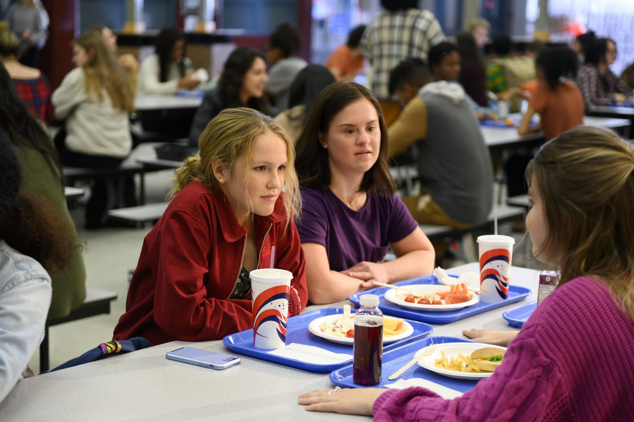 Alexis sitzt in der Schulkantine mit ihren Freundinnen, auf dem Tisch steht ihr Essen | Away