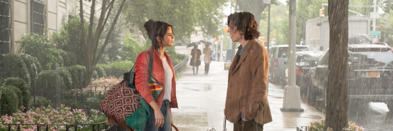 Shannon, gespielt von Selena Gomez, und Gatsby, gespielt von Timothée Chalamet, stehen im strömenden Regen auf der Straße. Gatsbys Schirm ist zusammengefaltet, die Nässe scheint beide nicht zu stören.