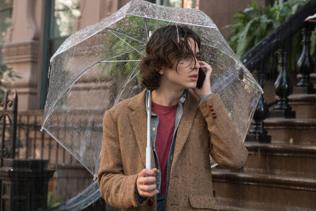 Gatsby, gespielt von Timothée Chalamet, steht in A Rainy Day in New York unter einem Schirm im strömenden Regen, sein Handy an der Wange.